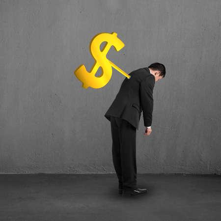 winder: Businessman with money symbol winder on his back concrete building interior Stock Photo