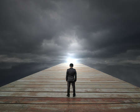 Businessman standing on wooden way face bright spot with cloudy sky
