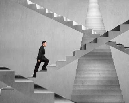 Businessman climbing on concrete stair maze with concrete wall background
