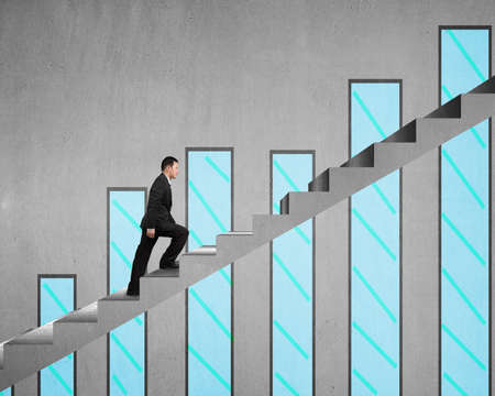 Businessman climbing on concrete stair with chart on concrete wall
