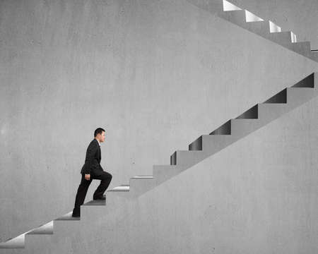 concrete stairs: Businessman climbing on concrete stairs with concrete wall