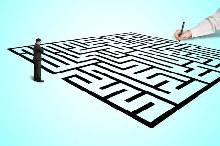 Hand drawing maze with thoughtful businessman standing photo