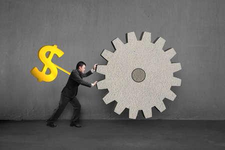 winder: Golden money shape winder on businessmans back rotating large concrete gear in concrete
