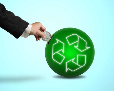 Hand hold coin insert into ball with recycling symbol in blue