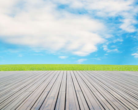 wood floor with green meadow, cloud and blue sky photo