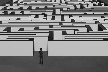 Businessman standing and facing huge maze structure with concrete background Stock Photo - 25039464