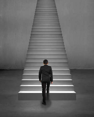 Rear view businessman climbing on stairs with spot lighting and concrete background