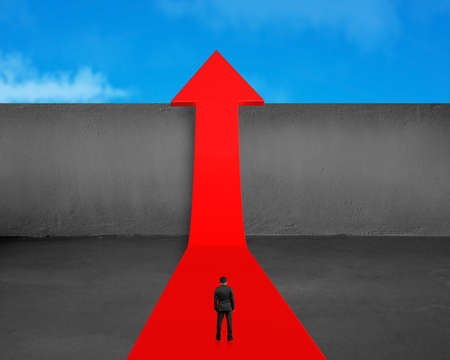 Rear view businessman standing on growing red arrow with concrete wall and blue sky  photo