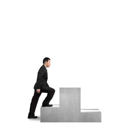 the first step: Businessman climbing on podium isolated in white background