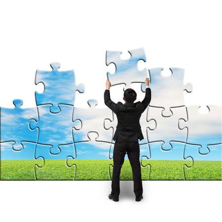 toma de decisiones: El hombre de negocios sostenga puzzles para montaje en fondo blanco Foto de archivo