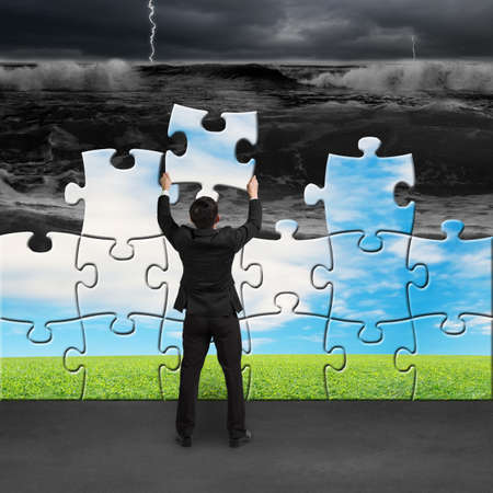Businessman holding puzzles to assembly change situation from tsunami to beautiful landscape
