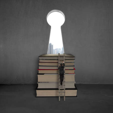 Businessman climbing to top of books with key shape door and city view outside
