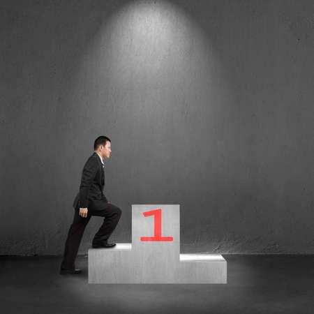 Businessman climbing on podium with spot light interior concrete background photo