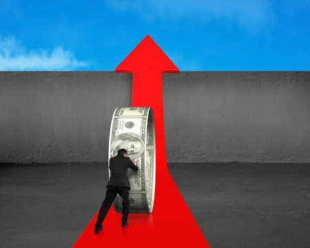 Businessman pushing money circle on growing red arrow with concrete wall and blue sky background photo
