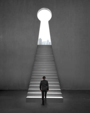 Businessman climbing on stair to key shape door with city view photo
