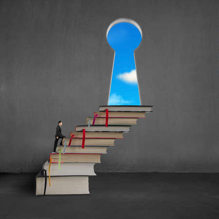 Businessman climbing on stack books to key shape door on concrete wall with blue sky outside photo