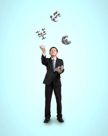 Businessman throwing and catching 3D sliver money symbols photo