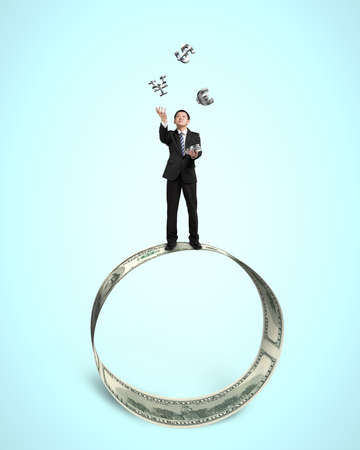 Businessman throwing and catching 3D sliver money symbols on money circle in blue background photo