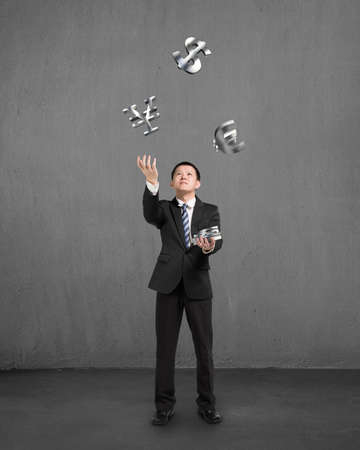 Businessman throwing and catching 3D sliver money symbols with concrete background photo