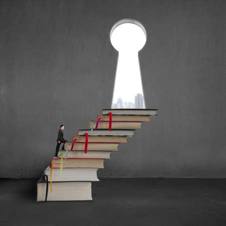Businessman climbing on stack books to key shape door with city view photo