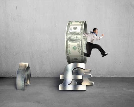 Businessman jumping through circle on stack money symbols interior concrete background photo