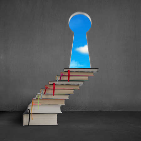 concrete stairs: Book stairs to key shape door on concrete wall with blue sky outside