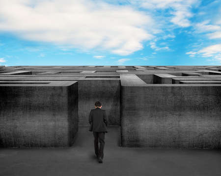 Rear view businessman walking toward to 3D concrete Maze with blue sky photo