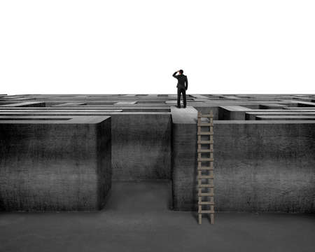 Businessman gazing on top of 3D concrete maze structure isolated in white  photo