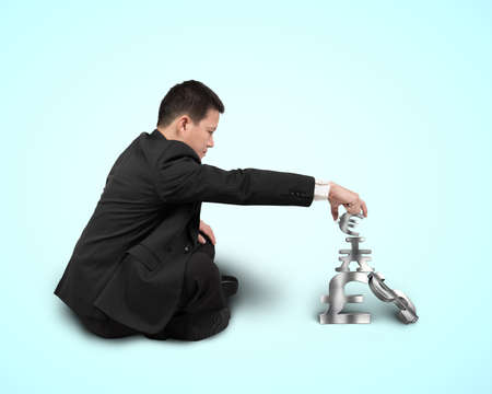 Businessman sitting and stacking sliver 3D symbols isolated in blue  photo