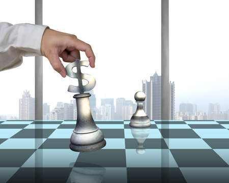 Hand allocating USD 3D symbol piece on chessboard with pawn and city view outside photo