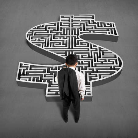 Businessman standing in front of 3d money shape maze on concrete ground photo