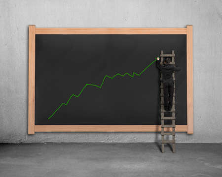 Businessman on ladder drawing growing green arrow trend on black board photo