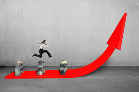 Businessman jumping over money symbols on growing red arrow with concrete  photo