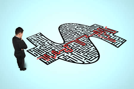 Businessman thinking in front of money shape maze with red route solution Stock Photo