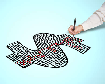 Hand drawing solution route on money shape maze in blue  photo