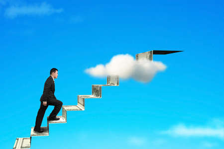 businessman on money stairs to top with blue sky background photo