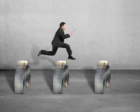 steeplechase: businessman jumping over euro symbol concrete background Stock Photo
