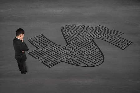 Businessman facing money symbol maze on concrete ground photo