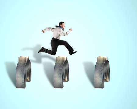 steeplechase: businessman jumping over euro obstacles isolated in blue background