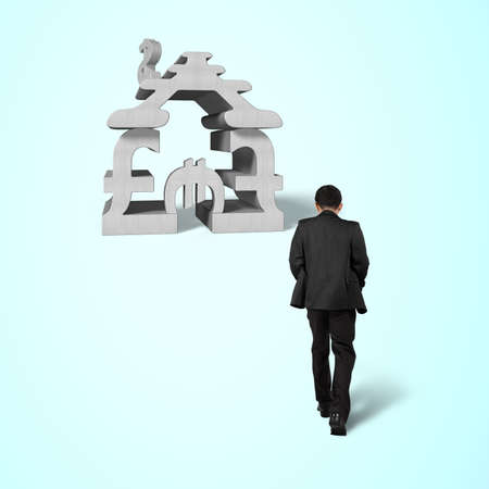 Walking toward concrete money symbol stacking building isolated in blue background photo