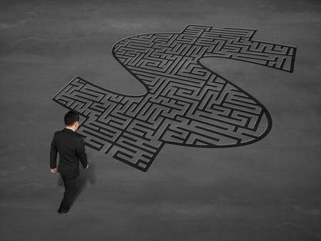 Businessman walking toward money shape maze on concrete ground photo