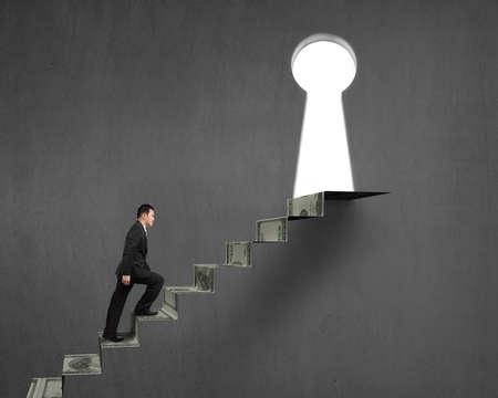 key hole: man climbing on money stairs to key hole on concrete wall