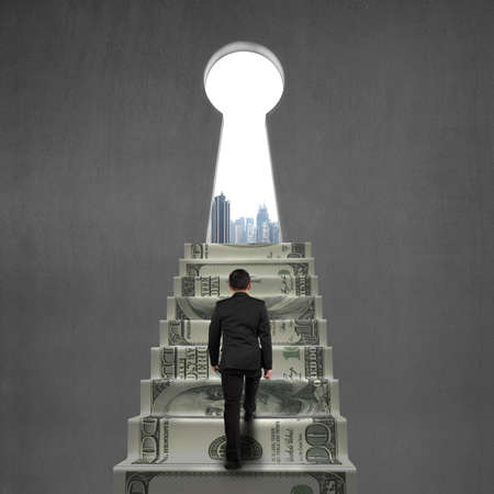 key hole: Man climbing on money stairs to key hole with city view
