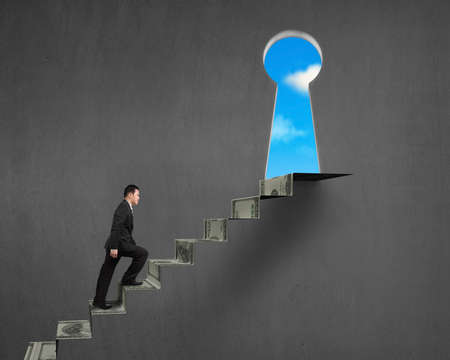 Walking on money stairs to key hole with blue sky outside Stock Photo
