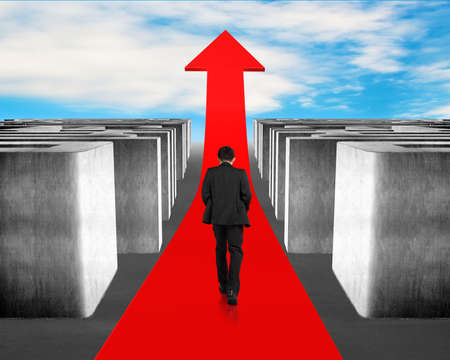 Businessman walking on growing red arrow through 3d Maze with blue sky background photo