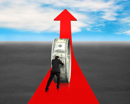 hard work: Man pushing money circle on red arrow blue sky background Stock Photo