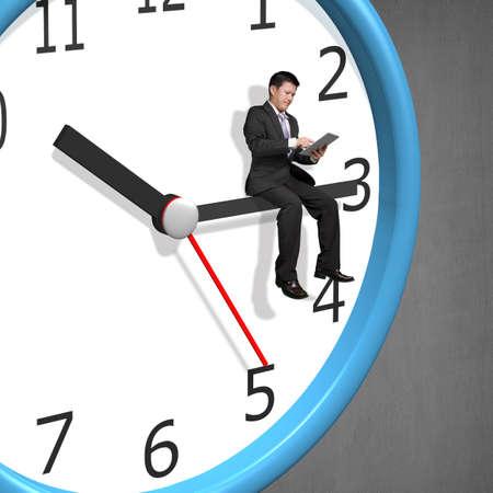 dispassionate: Businessman sitting on clock pointer concrete wall Stock Photo