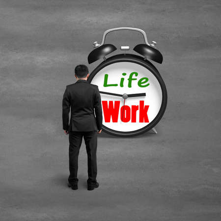 Standing toward alarm clock with life and work face on concrete ground photo
