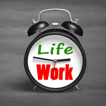 Alarm clock with life and work face on concrete ground photo