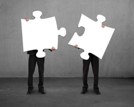 piezas de rompecabezas: Hombres que sostienen dos puzzles de concreto